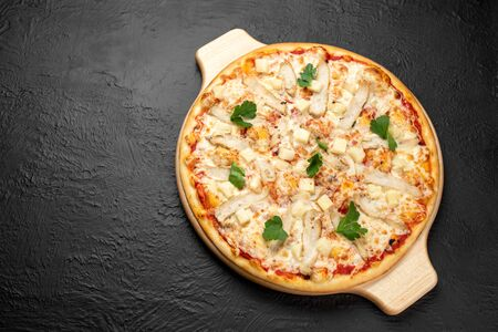 Pizza on a black background on a tomato base with mozzarella, grilled chicken, pineapples and parsley, there is a place for the inscription,Delicious 版權商用圖片
