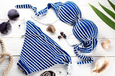 Separate blue and white striped swimsuit on a white wooden background of boards, next to accessories, shells, glasses, earrings cool