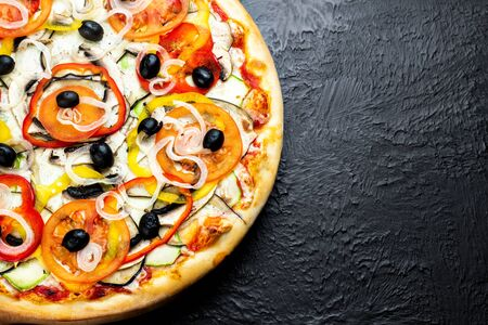 VEGETARIAN pizza on a black background, tomato-based with mozzarella, olives, tomatoes, eggplant, sweet pepper, zucchini, onion and mushrooms on a wooden stand