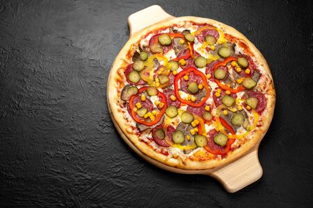 Mexican pizza on a black background, tomato-based with mozzarella, salami, beef, hot and sweet peppers, corn, and lightly salted cucumber on a wooden stand