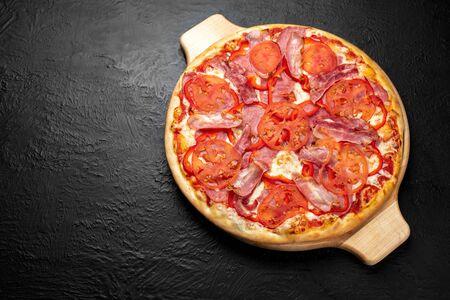 VESUVIO pizza on a black background, tomato-based with mozzarella, ham, bacon, tomatoes and bell pepper on a wooden stand 版權商用圖片