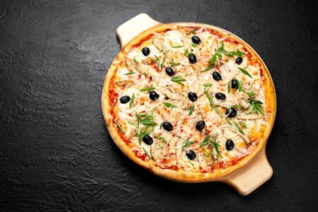 Pizza VENICE on a black background, tomato-based with mozzarella, grilled chicken, olives,green and onion on a wooden stand 版權商用圖片