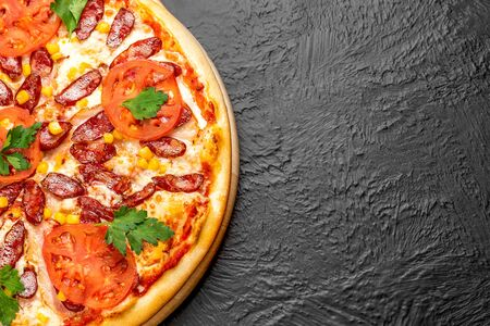 Hunting pizza on a black background, tomato-based with mozzarella, bacon, hunting sausages, parsley, tomatoes and corn on a wooden stand