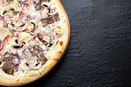BBQ pizza on a black background, on a cream base in combination with mozzarella, veal BBQ, bacon, mushrooms, red pickled onions,Delicious