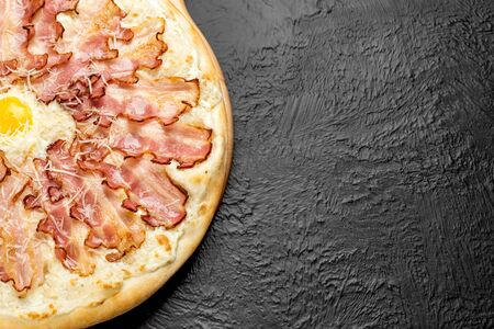 CARBONARA pizza on a black background, cream-based with mozzarella, bacon, Parmesan, garlic and egg on a wooden stand