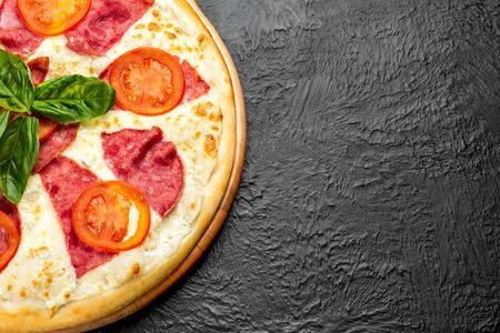 Pizza on a black background on a creamy base combined with mozzarella, ham, tomatoes and fresh Basil or parsley Delicious