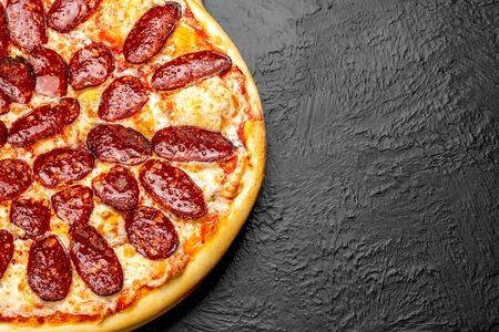 PEPPERONI pizza on a black background, tomato-based with mozzarella and spicy salami Napoli on a wooden stand 版權商用圖片