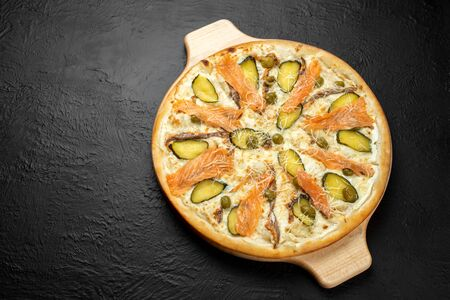SAN MARINO pizza on a black background, cream-based with mozzarella, Parmesan, salmon, pickle and olives,Delicious