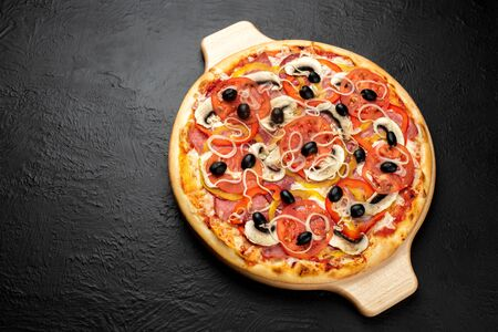 Pizza on a black background, tomato-based with mozzarella, ham, salami, olives, tomatoes, sweet peppers, onions and mushrooms,Delicious 版權商用圖片