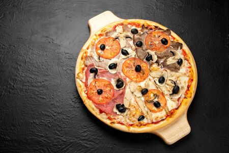 Pizza FOUR FLAVORS on a black background, tomato-based with mozzarella, veal, ham, olives, tuna, chicken, mushrooms and tomatoes on a wooden stand