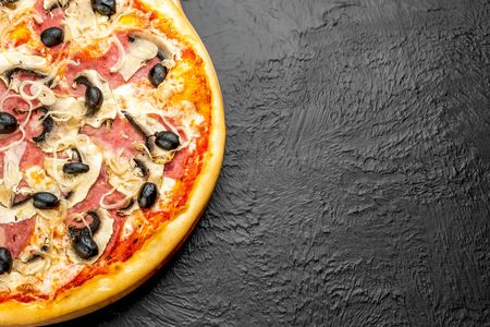Milanese pizza on a black background, tomato-based with mozzarella, ham, mushrooms, onions and olives,Delicious 版權商用圖片