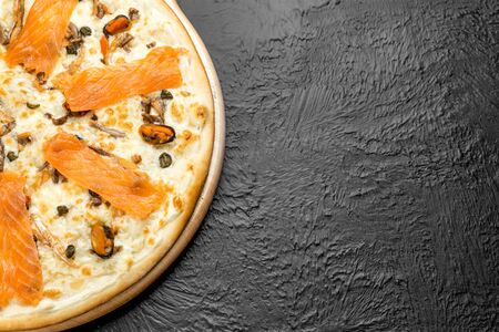 Pizza NAPLES on a black background, cream-based with mozzarella, mussels, lightly salted salmon and capers on a wooden stand