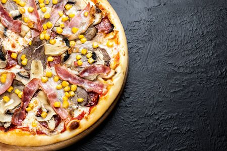 VIENNESE pizza on a black background, tomato-based with mozzarella, veal, chicken fillet, bacon, Napoli salami, corn and mushrooms on a wooden stand