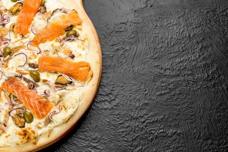 SEA pizza on a black background, cream-based with mozzarella, lightly salted salmon, mussels, squid, cocktail shrimp, octopus, olives and red onion on a wooden stand