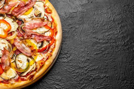 SPICY pizza on a black background, tomato-based with mozzarella, sweet pepper, salami, bacon, mushrooms, onion, garlic, eggplant and chili, Delicious 版權商用圖片