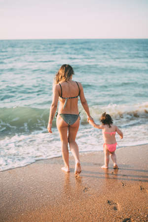 Mother and daughter in swimsuits go to the sea cute