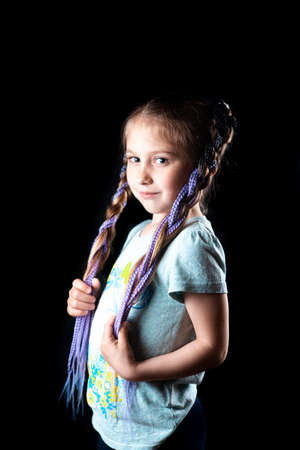 A small girl on a black background with purple Afro elastic bands, pigtails on an elastic band tied two tails cool Фото со стока