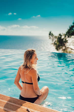 Charming, sexy girl sitting by the pool, which is on the background of the sea, cool