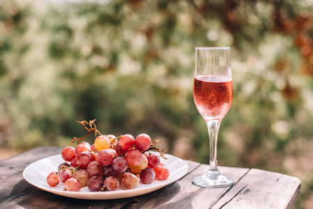 A glass of champagne or wine next to pink grapes is placed on a wooden table against a background of pine and juniper forests cool 版權商用圖片