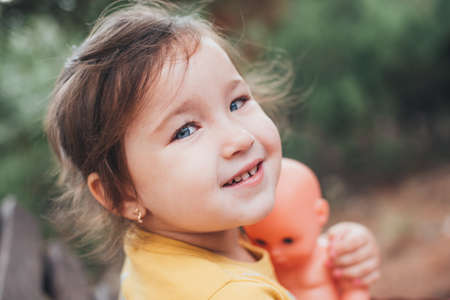 Portrait of a cute Little girl with blue eyes in nature with a baby doll in her hands 版權商用圖片