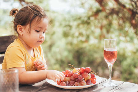 Little cute girl eating pink grapes sitting on a wooden bench in the woods in the summer in nature cool