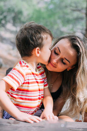 Son kisses mother in the forest in nature, sincere emotions cool