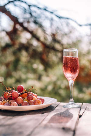 A glass of champagne or wine next to pink grapes is placed on a wooden table