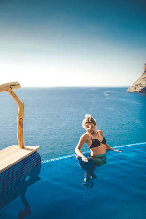 Beautiful girl on the edge of the pool, behind a beautiful spectacular view of the sea and mountains .Luxury