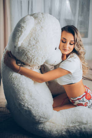 A woman with a huge teddy bear on the bed