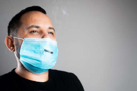 A man smokes through a medical mask after making 版權商用圖片