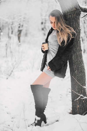 Beautiful young girl in a fur coat dress and high boots in the winter in the forest with coffee