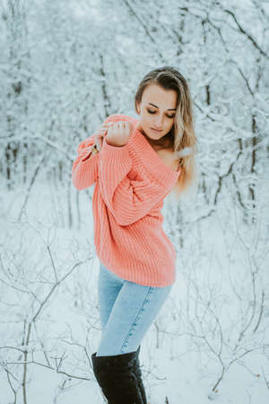 Beautiful young girl in a pink voluminous sweater and jeans in a cold snowy forest