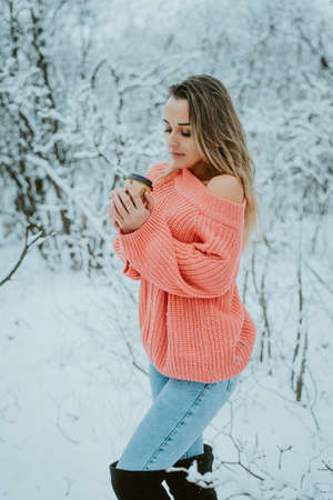 Beautiful young girl in a pink voluminous sweater and jeans with coffee in her hands in a cold snowy forest