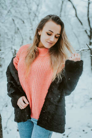 Beautiful young girl in a fur coat pink voluminous sweater and jeans in a cold snowy forest