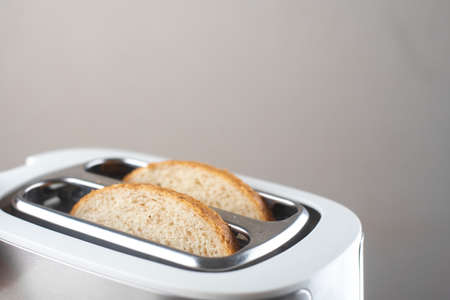 A white and silver toaster on a gray background with pieces of bread sticking out