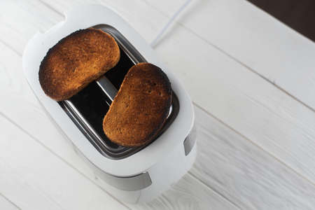 A white and silver toaster on a gray background with burnt bread 版權商用圖片