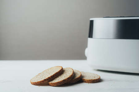 A white and silver toaster sits on a white wooden table with slices