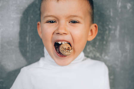 A boy child tries to crack a walnut showing healthy strong baby teeth, makes an effort