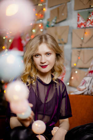 Close portrait of a cute lady with Christmas lights, looking at the camera 2020