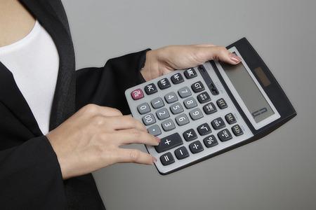 oversight: business woman using calculator