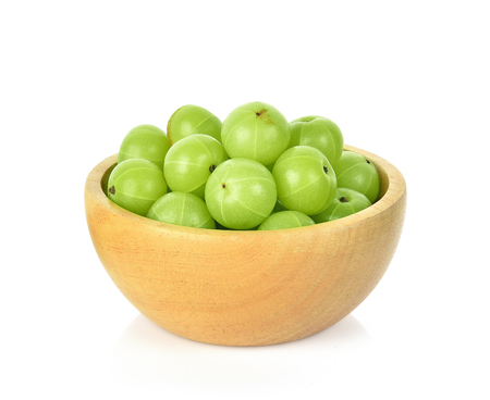 Indian gooseberry in wooden bowl isolated on white background Stockfoto