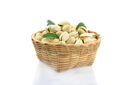 Pistachio and green leaf in bamboo basket isolated on white background