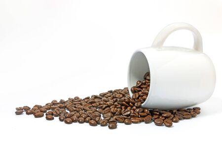 Granos de café en taza blanca sobre fondo blanco.