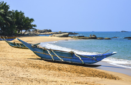 Turquoise blue fishing boat at sunrise on the beach in Sril Lanka, India Stock Photo