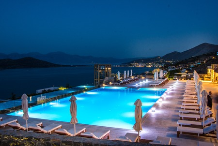 fishingboats: Panoramic view on night swimming pool in Royal Marmin Bay Boutique Hotel at Elounda City, Crete, Greece Stock Photo