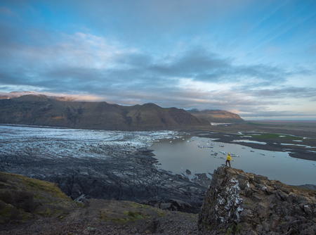 hiking in winter, backpacker enjoying panoramic landscape of glacier in Iceland at sunset in national park Skaftafell
