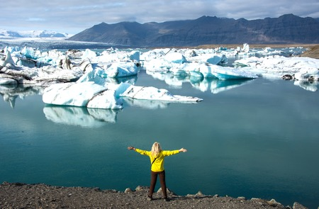 The woman - tourist watching the moving ice. Sunrise in the Ice Lagoon.