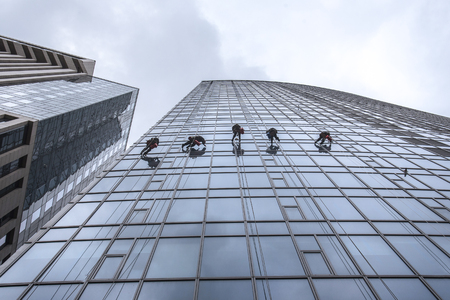 Window washers cleaning the glass facade of a skyscraper, high risk work. Gulliver tower in Kiev, Ukraine