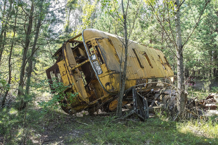 Abandoned and rusty bus in a field in a sunny day with blue sky and clouds in the Chernobyl nuclear power plant zone of alienation