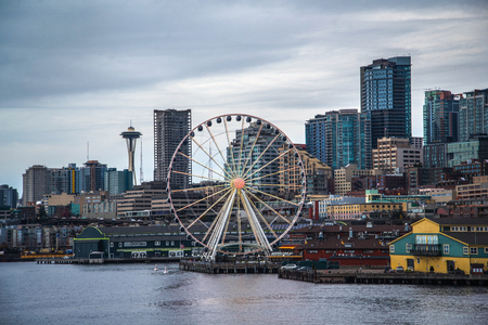 Seattle waterfront and skyline, with the Space Needle showing through the spokes of the Great Wheel ferris wheel in the foreground. Colorful image with late afternoon gold light. 版權商用圖片